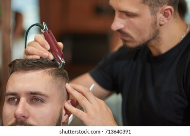 Cropped shot of a professional barber working using a clipper styling hair of his client.