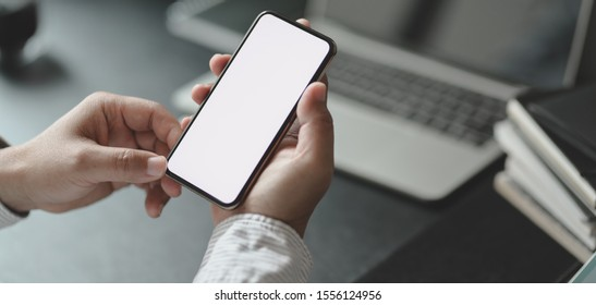 Cropped shot of professional businessman holding blank screen smartphone in dark modern office room