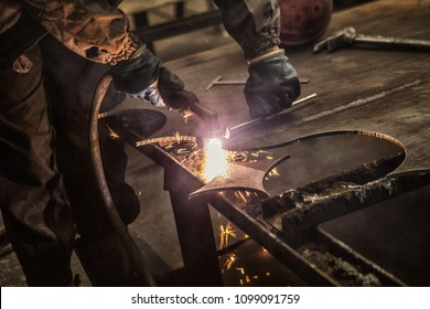 Cropped shot of a professional metalworker cutting steel sheet with a manual plasma cutting machine. Indsutrial worker welding metal at the factory. Heavy industry, employment, labor concept