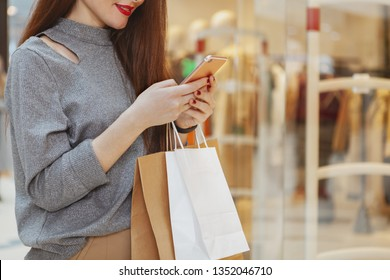 Cropped shot of a red lipped woman smiling, using smart phone while shopping at the mall. Female customer with shopping bags browsing online on her phone, copy space