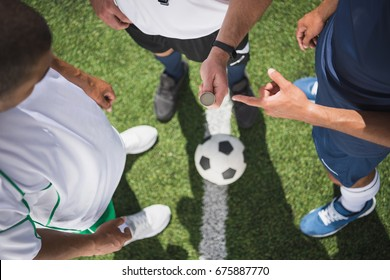 cropped shot of referee holding coin before start of soccer match on pitch