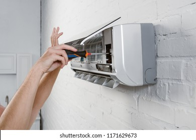 cropped shot of repairman taking off filter from conditioner with screwdriver