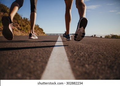 Cropped shot of runners running on the road. Rear view close-up image of man and woman jogging outdoors. Focus on road and legs of athlete.