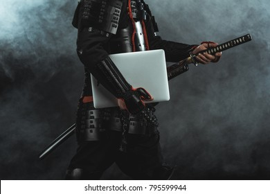 cropped shot of samurai in traditional armor with laptop taking out sword on dark background with smoke