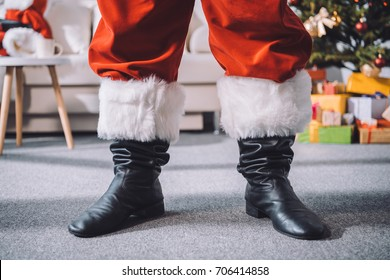 cropped shot of santa claus in black boots standing in room
