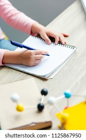 cropped shot of schoolchild taking notes while studying with books and molecular model
