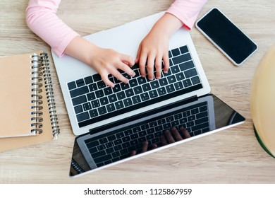 cropped shot of schoolchild using laptop with blank screen
