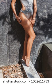cropped shot of seductive woman in grey swimsuit with tanned legs