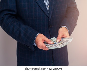 Cropped shot of senior businessman holding dollar bills in hands. Man counting money.