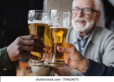 cropped shot of senior friends clinking glasses of beer