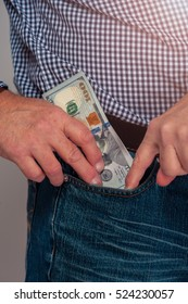 Cropped shot of senior man in casual cloth putting money to jeans pocket. Dollar bills in male hands.