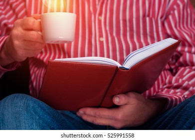 Cropped shot of senior man sitting with cup of drink and reading a book.