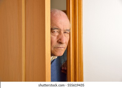 Cropped shot of senior man spying and entering through the door as concept of nosy man