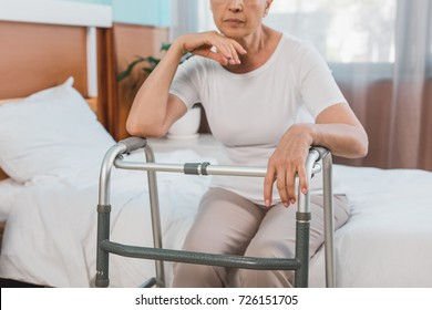 cropped shot of senior woman with walker sitting on hospital bed