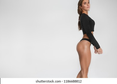 Cropped shot of sensual woman with braid demonstrating her sculpted butt wearing sports top and bikini standing isolated against white studio wall background with copy space for your text