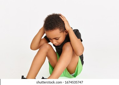 Cropped shot of serious fit sporty African boy in sports clothes sitting on floor with hands behind head doing sit ups or crunches to strengthen core muscles. Black child working out abdominal