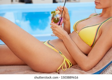 Cropped shot of a sexy woman in yellow bikini enjoying a drink at the poolside. Unrecognizable woman sunbathing near the swimming pool, drinking a cocktail