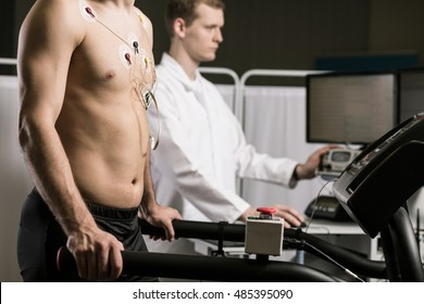 Cropped shot of a shirtless man with electrodes attached to his chest and young doctor in the background