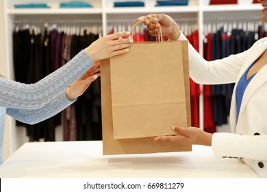 Cropped shot of a shop assistant handing shopping bags to a female customer copyspace buying buyer seller sale discount offer giving consumerism purchasing business lifestyle clothing boutique