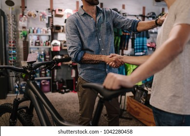 Cropped shot of shop owner giving a handshake to a customer after selling a bicycle.