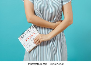 Cropped shot sickness woman in blue dress holding periods calendar for checking menstruation days put hand on tummy isolated on blue background. Medical, healthcare, gynecological concept. Copy space