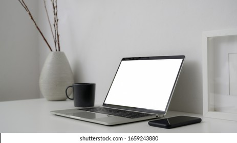 Cropped shot of simple workspace with blank screen laptop, smartphone and decorations on white desk with white wall background