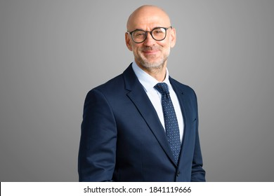 Aufnahme eines lächelnden Geschäftsmanns, der Anzug und Krawatte trägt, während er einzeln auf grauem Hintergrund steht. Kopiert Platz.