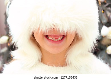 Cropped Shot Of A Smiling Girl Wearing A White Hat Over Christmas Tree Background. Face Of Little Girl. Happiness, Childhood, Christmas, Winter, Holidays Concept. Happy Toothless Girl Portrait.