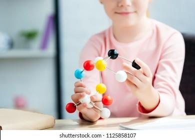 cropped shot of smiling schoolchild holding molecular model