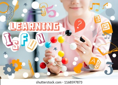 """cropped shot of smiling schoolchild holding molecular model, with icons and lettering """"learning is fun"""""""