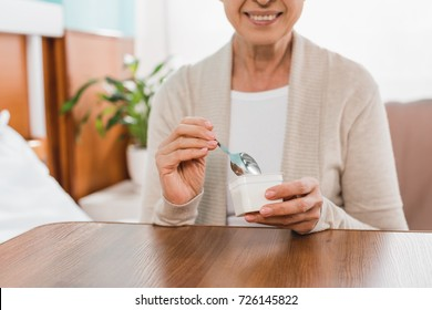 cropped shot of smiling senior woman eating yogurt in hospital