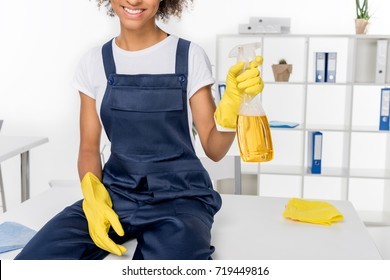 cropped shot of smiling young african american cleaner holding spray bottle