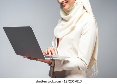 cropped shot of smiling young muslim woman using laptop isolated on grey
