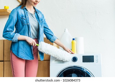 cropped shot of smiling young woman cleaning washing machine