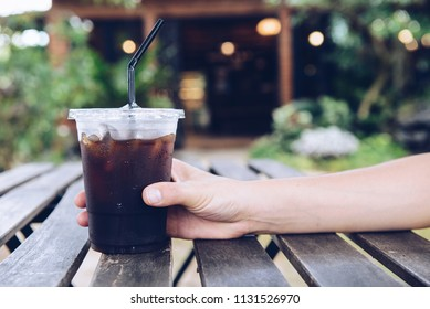 Cropped shot of someone hand touching a plastic cup of iced Americano (black coffee) on the wood plank table.