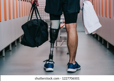 cropped shot of sportsman with artificial leg standing at gym changing room with towel and bag