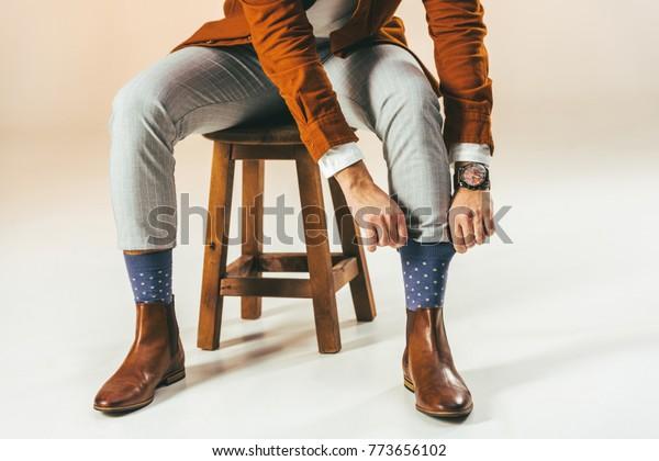 beschnittene Aufnahme von stylischen, männlichen Ziersocken während des Sitzens auf Holzstuhl auf Beige