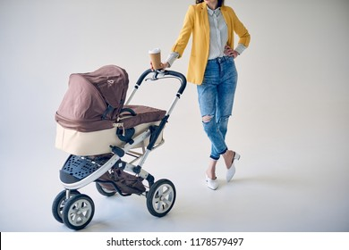 cropped shot of stylish woman holding disposable coffee cup and standing with baby stroller on grey