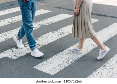 cropped shot of stylish woman in skirt and man in jeans walking on crosswalk at city street