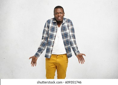 Cropped shot of stylish young Afro-American man shrugging shoulders gesturing with hands as if saying: so shat, who cares, having indignant expression on his face, posing at white studio wall