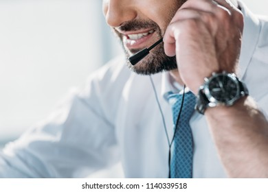 cropped shot of support hotline worker in shirt with tie talking by headphones with microphone