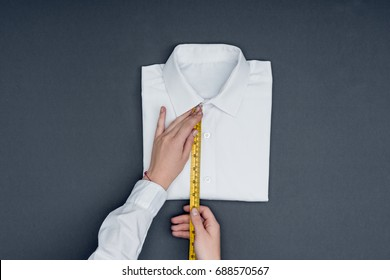 cropped shot of tailor measuring shirt with measuring tape isolated on grey