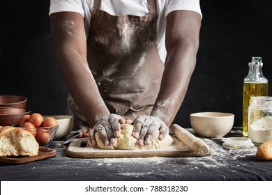 Cropped shot of talented dark skinned male cook kneads studiously dough, prepares for culinary competiton, isolated over black chalk background. African American male bakes something delicious