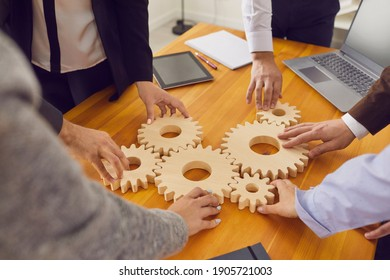 Cropped shot of team of company workers joining cogwheels on office table as metaphor for collaboration, teamwork, good business system, finding working solutions and effective management