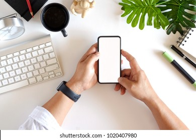 Cropped shot top view of businessman hands using smartphone mockup at the white office desk. Blank screen mobile phone for graphic display montage