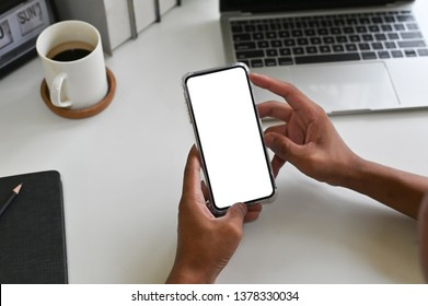 Cropped shot top view of businessman hands using smartphone mockup on office desk. Blank screen mobile phone for graphic display montage.