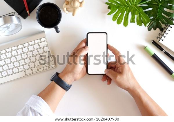 ホワイトオフィスのデスクでスマートフォンモックアップを使用して、ビジネスマンの手のショットトップビューを切り抜きました。グラフィックスディスプレイのモンテージ用の空白画面携帯電話