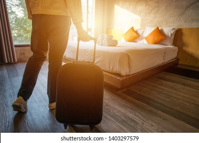 Cropped shot of tourist woman pulling her luggage to her hotel bedroom after check-in. Conceptual of travel and vacation.