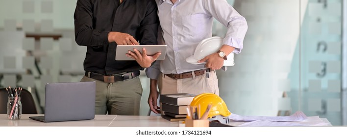 Cropped shot of two engineers working together with digital tablet, laptop and office supplies in meeting room