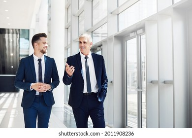 Cropped shot of two handsome businessmen having a discussion while walking through the office during the day - Shutterstock ID 2011908236